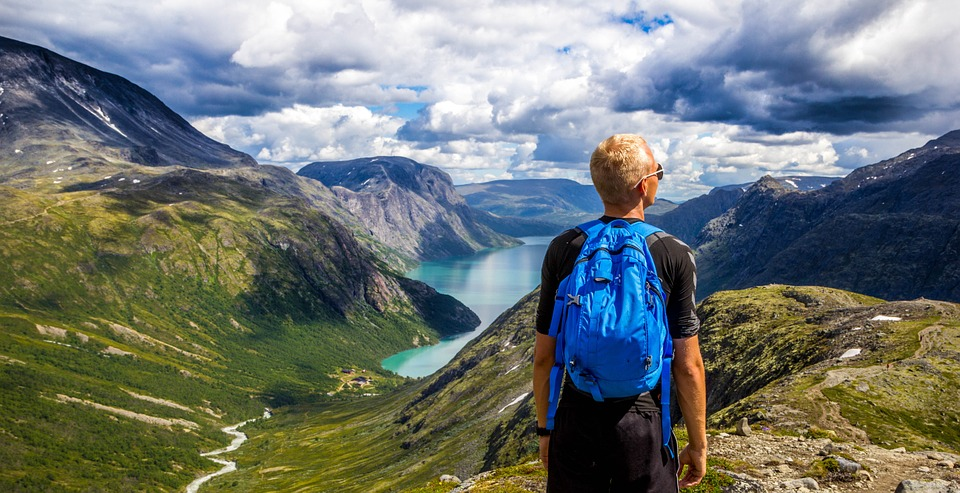 Man wearing blue backpack and hiking in honor of men's health month